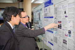Conference judges examine student poster